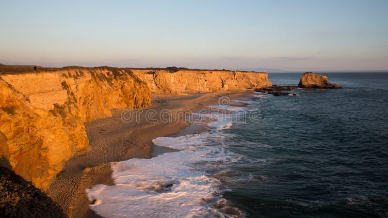 Zonsondergang op een strand met hoge klippen stock afbeelding