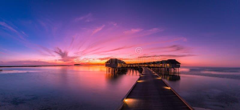 Zonsondergang op het eiland van de Maldiven, de villa'stoevlucht van het luxewater en houten pijler Mooie hemel en wolken en stra royalty-vrije stock foto's