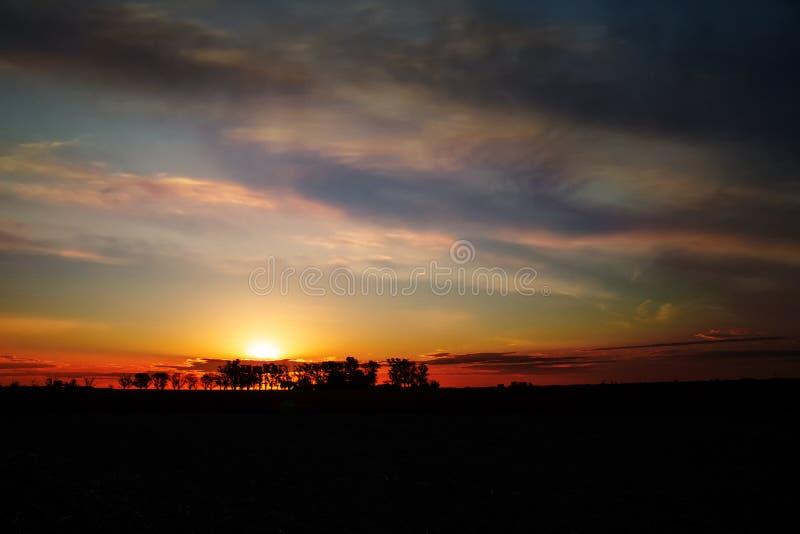 Zonsondergang op het gebied De zonreeksen achter de bomen royalty-vrije stock afbeeldingen