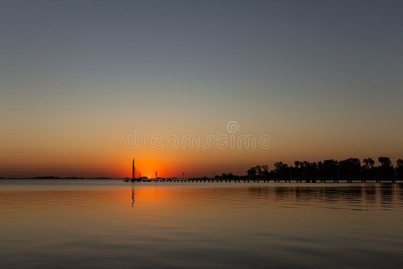 Zonsondergang op het meer De zon wijst op zijn licht op het meer stock afbeelding