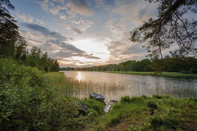 Zonsondergang op het meer in Zweden Groene aardkleuren en blauwe hemel met witte wolken Boot die op kust wordt geparkeerd royalty-vrije stock afbeeldingen