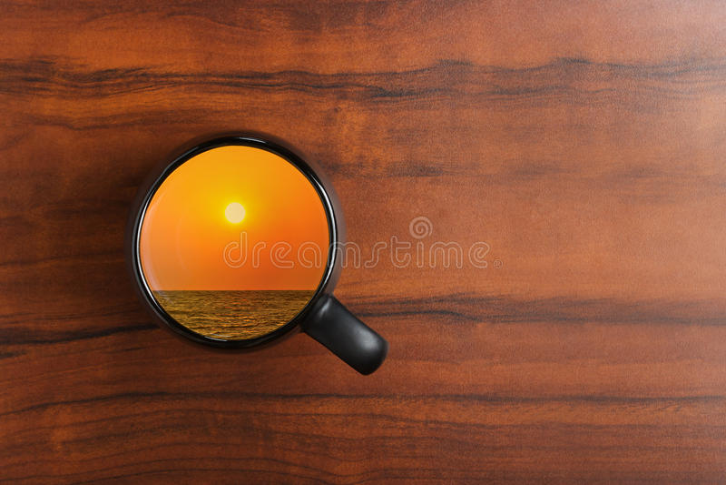 Zonsondergang op het overzees in een zwarte koffiekop royalty-vrije illustratie