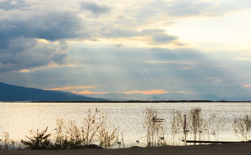 Zonsondergang op het overzees met wolken De zon tussen wolken royalty-vrije stock afbeelding