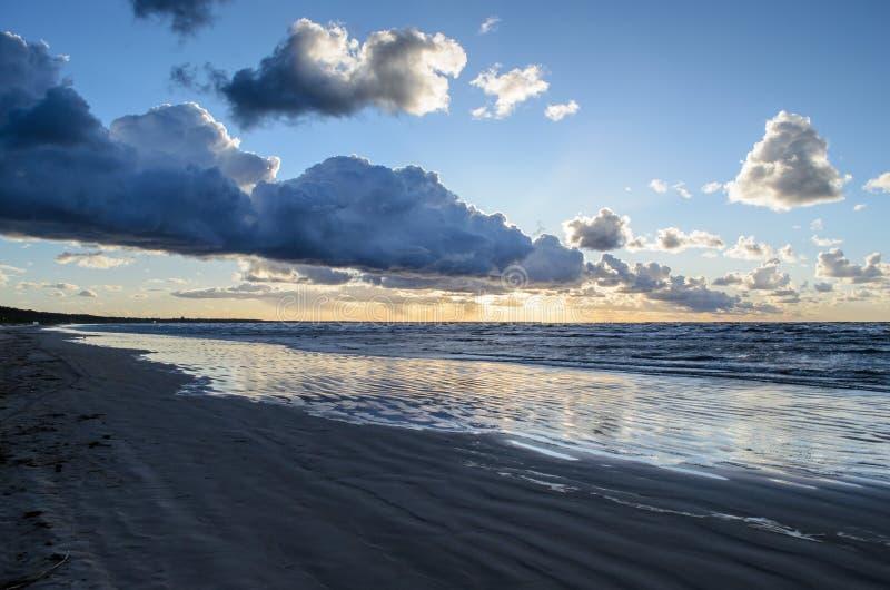 Zonsondergang op het strand met bewolkte hemel, Oostzee, Jurmala, Letland stock afbeeldingen
