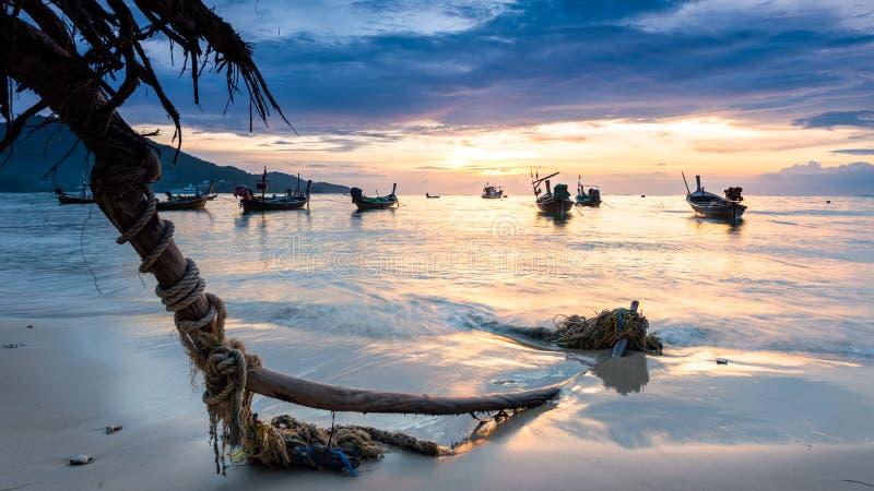 Zonsondergang op het strand met vissersboot in Phuket, Thailand stock afbeelding