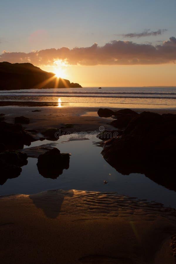 Zonsondergang op het strand van de Hoopinham, Devon, het Verenigd Koninkrijk stock afbeelding