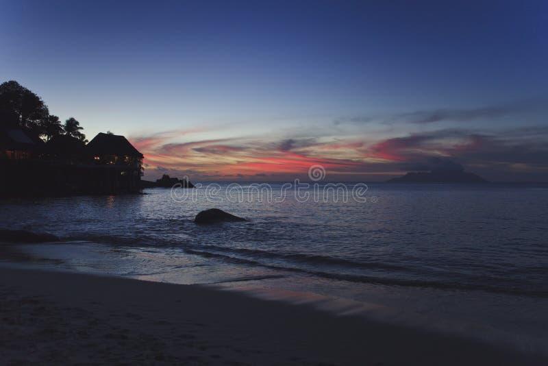 Zonsondergang op het strand van een tropisch eiland Op de kust van sommige kleine eilandhuizen royalty-vrije stock foto