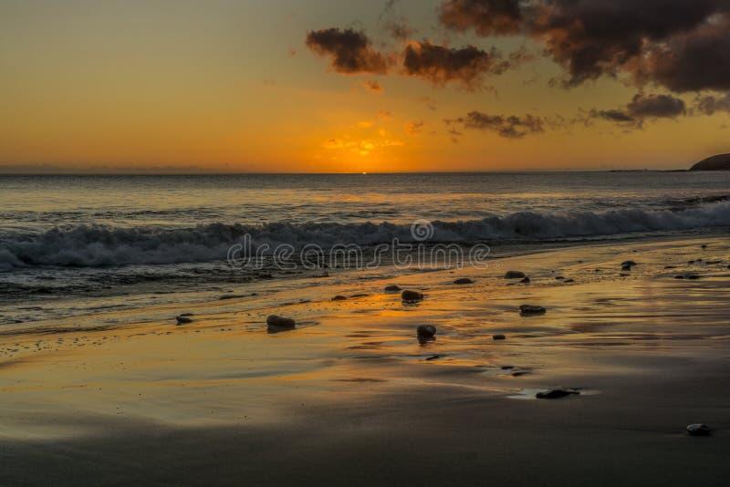 Zonsondergang op het strand van Fuerteventura met lavarotsen royalty-vrije stock foto