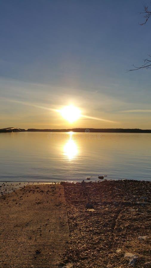 Zonsondergang op het water stock afbeelding