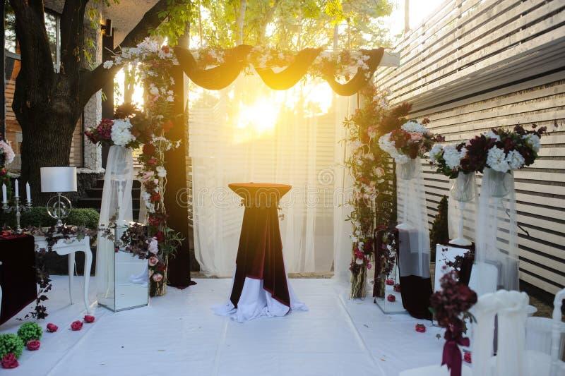 Zonsondergang op huwelijksontvangst met rood/Bordeauxbloemen wordt verfraaid die royalty-vrije stock afbeeldingen