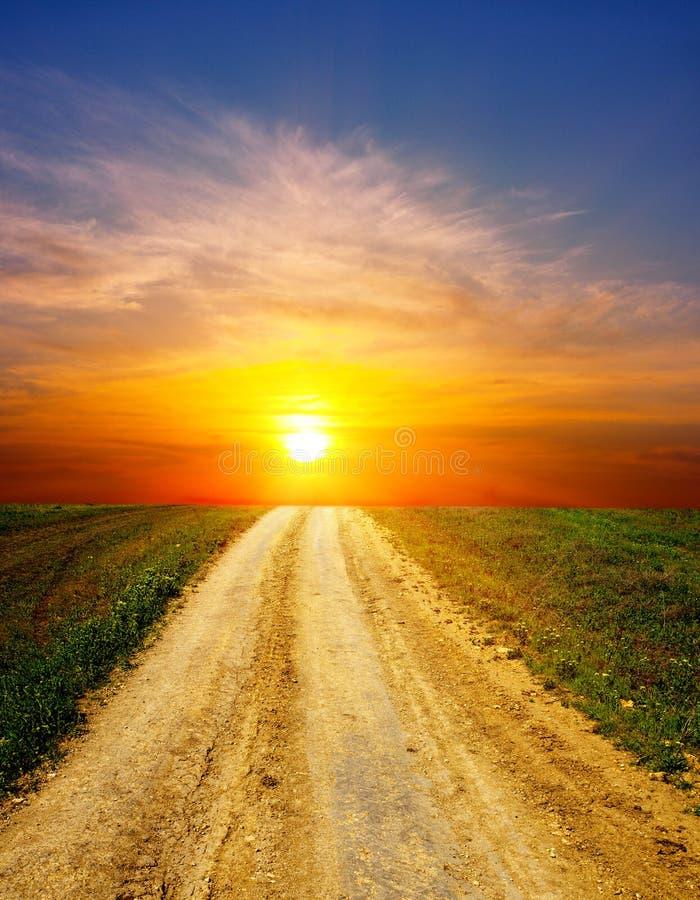 Zonsondergang op landelijke weg royalty-vrije stock afbeelding