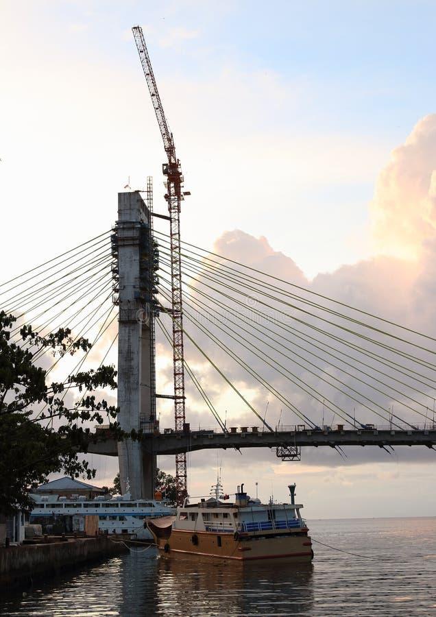 Zonsondergang op onvolledige brug in Manado stock foto