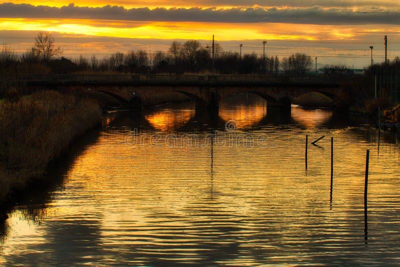 Zonsondergang op rivier onder oude spoorwegbrug stock fotografie