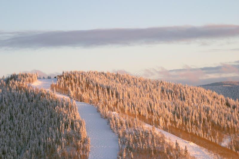 Zonsondergang op skihellingen bij de winter stock afbeeldingen