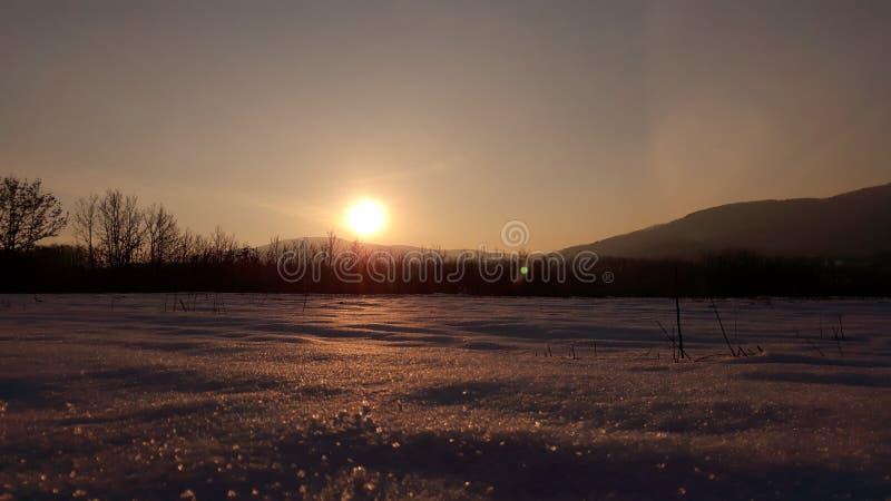 Zonsondergang op sneeuwland stock fotografie