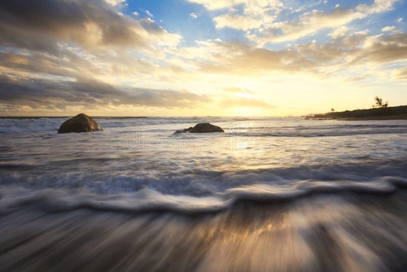 Zonsondergang op strandgolven en rotsen royalty-vrije stock fotografie