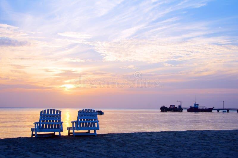 Zonsondergang op van de het strandzitkamer van het Picknickcentrum de stoelen en de boten in distan stock afbeeldingen