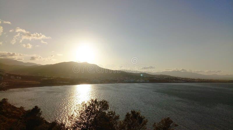 Zonsondergang op zee dorp stock foto