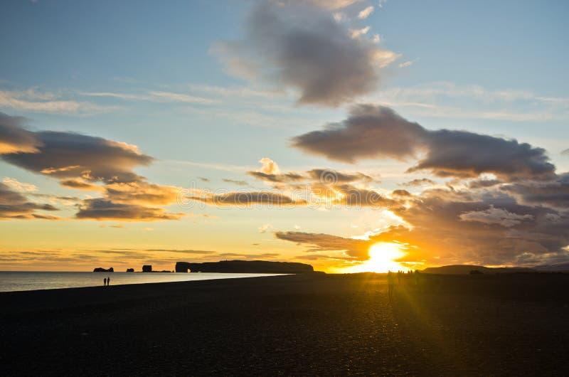 Zonsondergang op zwart strand met Dyrholaey-rots op achtergrond, IJsland royalty-vrije stock foto