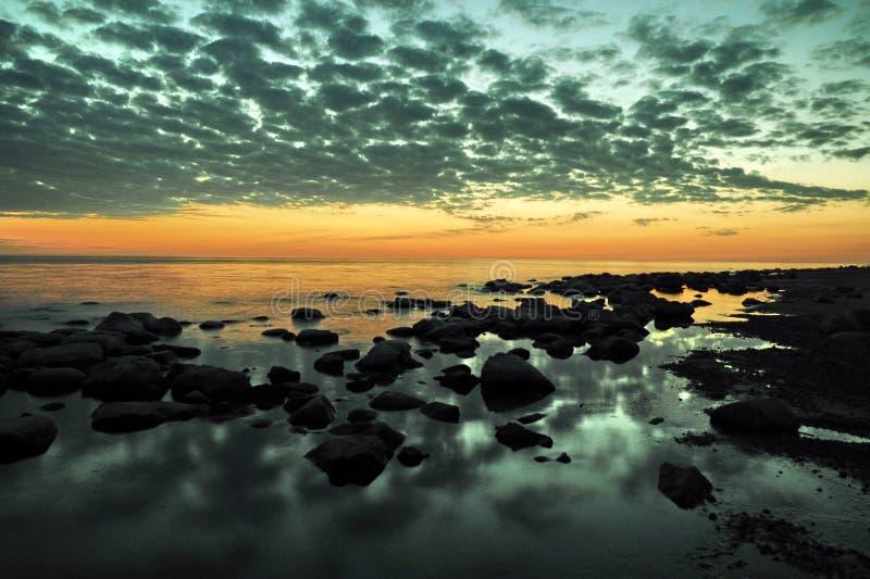 Zonsondergang oranje en blauwe wolken op hemel over overzeese kust stock foto's