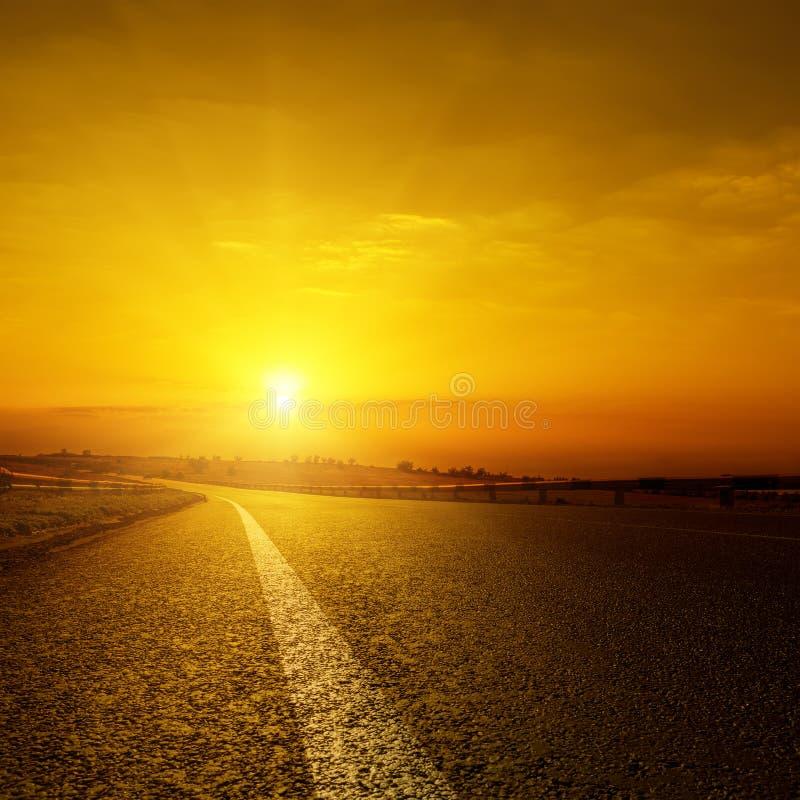 Zonsondergang over asfaltweg stock foto