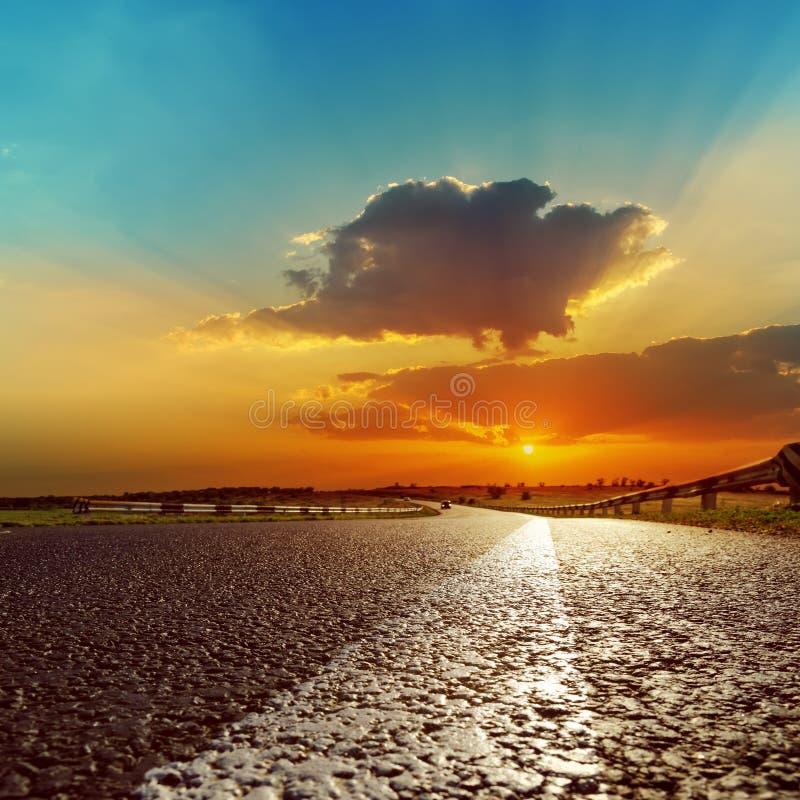 Zonsondergang over asfaltweg stock afbeeldingen
