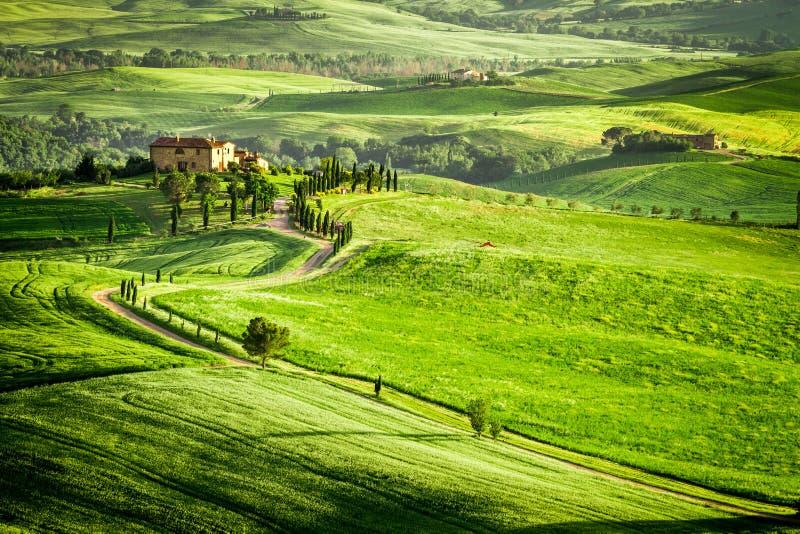 Zonsondergang over boerderij in Toscanië op een heuvel wordt gevestigd die royalty-vrije stock afbeelding
