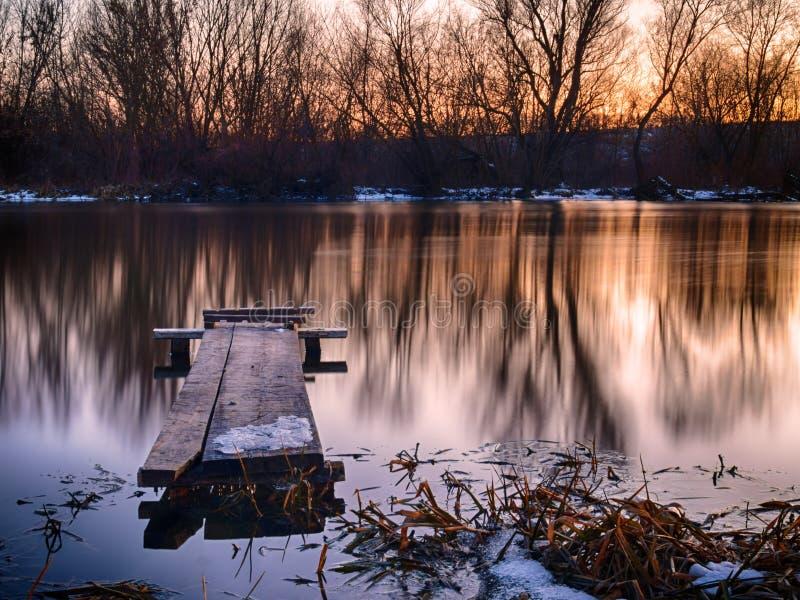 Zonsondergang over de de winterrivier stock afbeelding