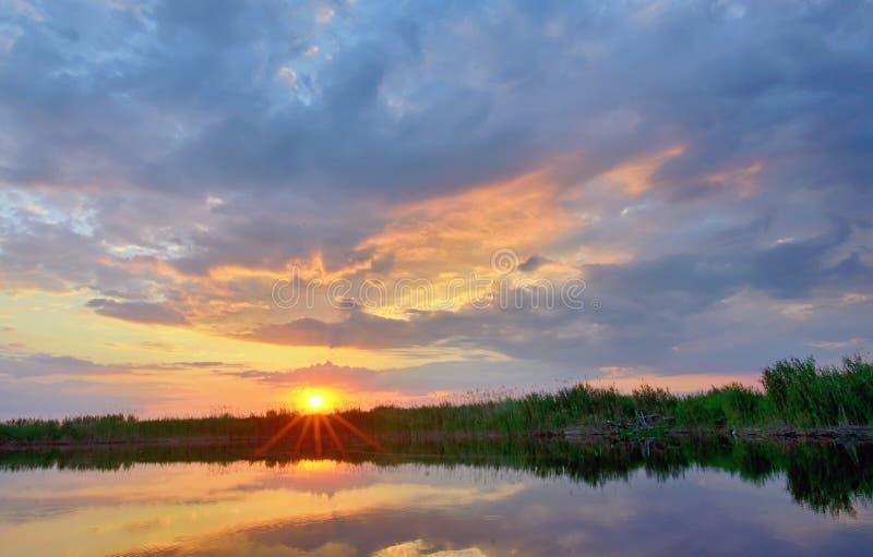 Zonsondergang over de delta van Donau stock foto