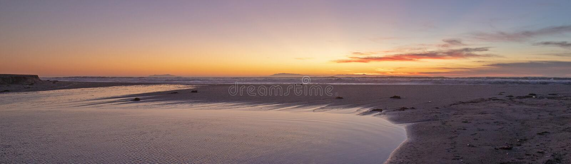 Zonsondergang over de getijdeafvloeiing van Santa Clara River aan Vreedzame Oceaan bij McGrath-het Park van de Staat op de kust v stock foto