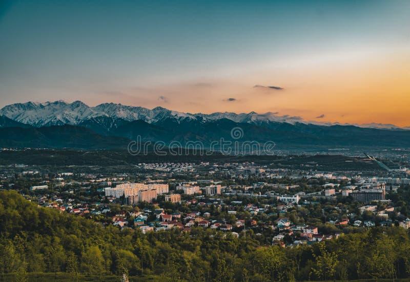 Zonsondergang over de stad van Alma Ata en een mening van de Toren van TV van Kok Tobe stock foto