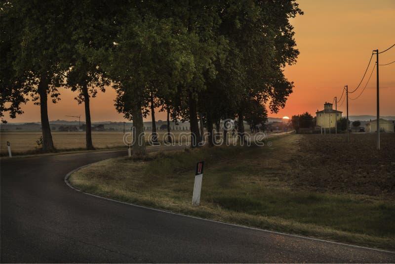 Zonsondergang over de weg - Toscanië stock afbeelding
