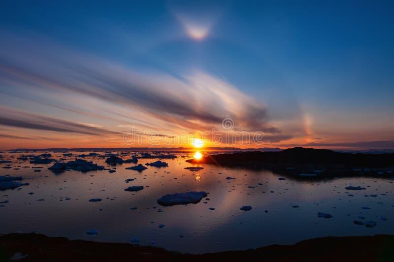 Zonsondergang over Disko-Baai in Groenland met cirkelhaloeffect stock fotografie