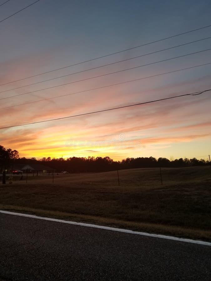 Zonsondergang over een breed weiland door een weg stock afbeeldingen