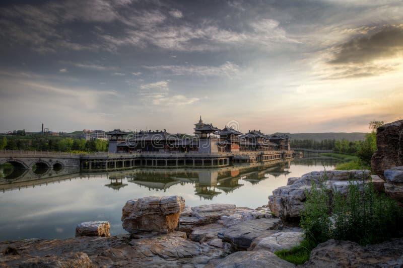 Zonsondergang over een Chinees stijlkasteel in een meer met een brug en rotsen in de voorgrond stock afbeelding