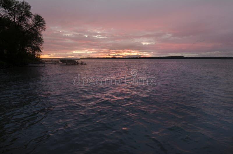 Zonsondergang over een Meer in Minnesota met Enige Boot royalty-vrije stock afbeeldingen