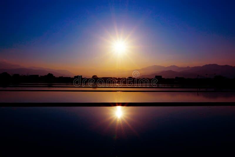 Zonsondergang over een padiegebied stock foto