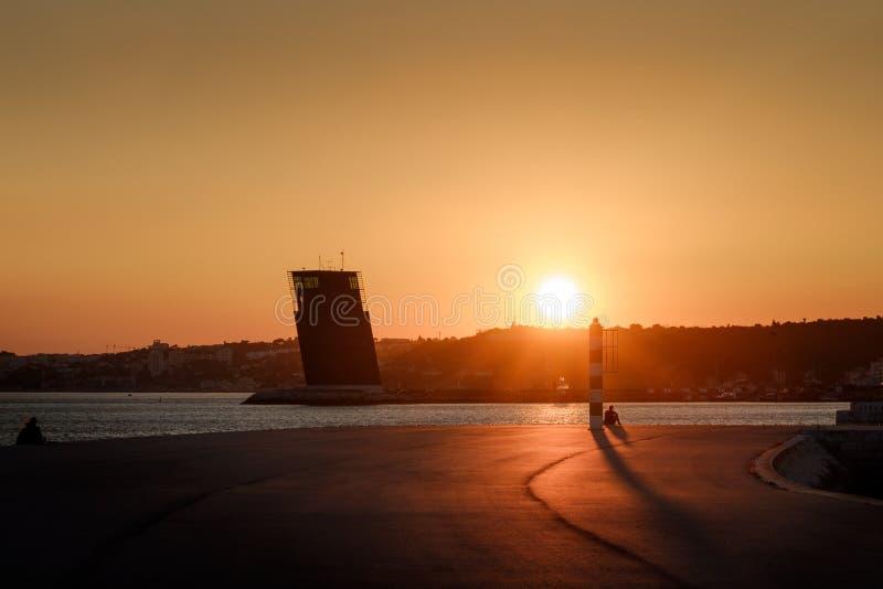 Zonsondergang over een pijler in Lissabon stock foto