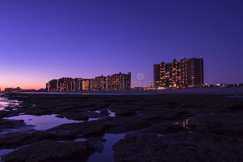 Zonsondergang over een rotsachtig strand vooraan de hotels royalty-vrije stock foto