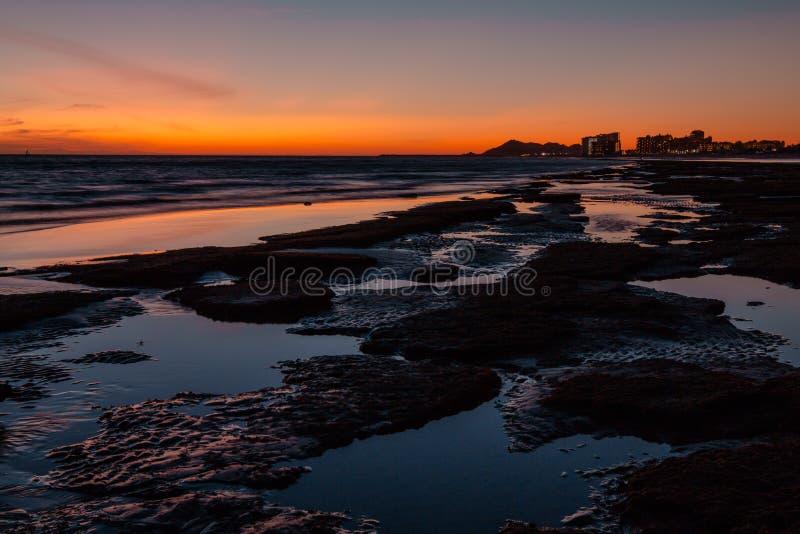 Zonsondergang over een rotsachtig strand vooraan de hotels stock foto