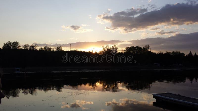 Zonsondergang over een rustig meer stock afbeelding