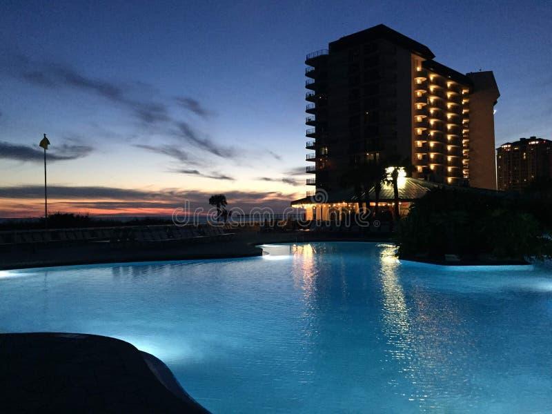 Zonsondergang over een zwembad met een groot gebouw op de achtergrond stock fotografie