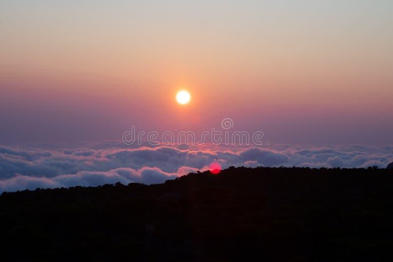 Zonsondergang over heemstwolken met lensgloed stock fotografie