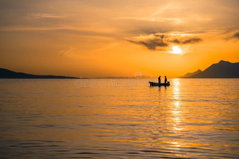Zonsondergang over het Adriatische overzees met een kleine vissersboot, Makarska, Kroatië stock foto's