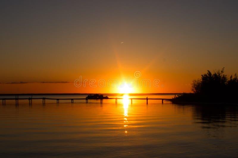 Zonsondergang over het dok bij het meer stock foto