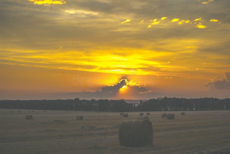 Zonsondergang over het gebied hooiberg stock foto's