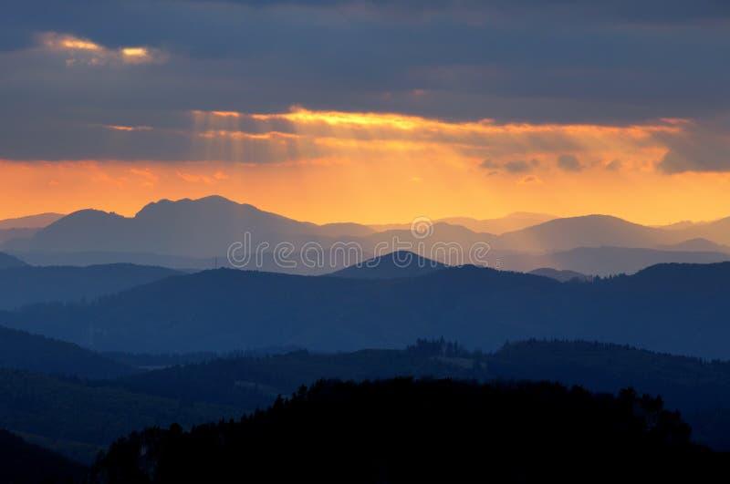 Zonsondergang over het silhouet van de kleurenberg stock fotografie