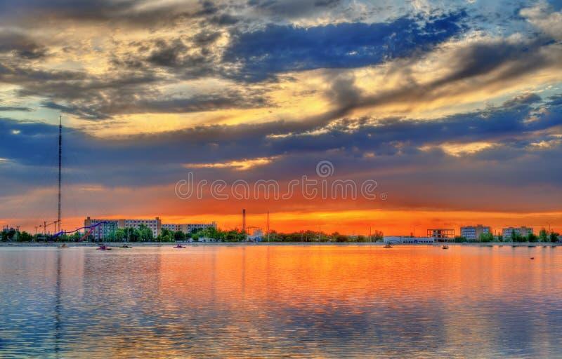 Zonsondergang over het stadsmeer in Navoi, Oezbekistan stock afbeeldingen