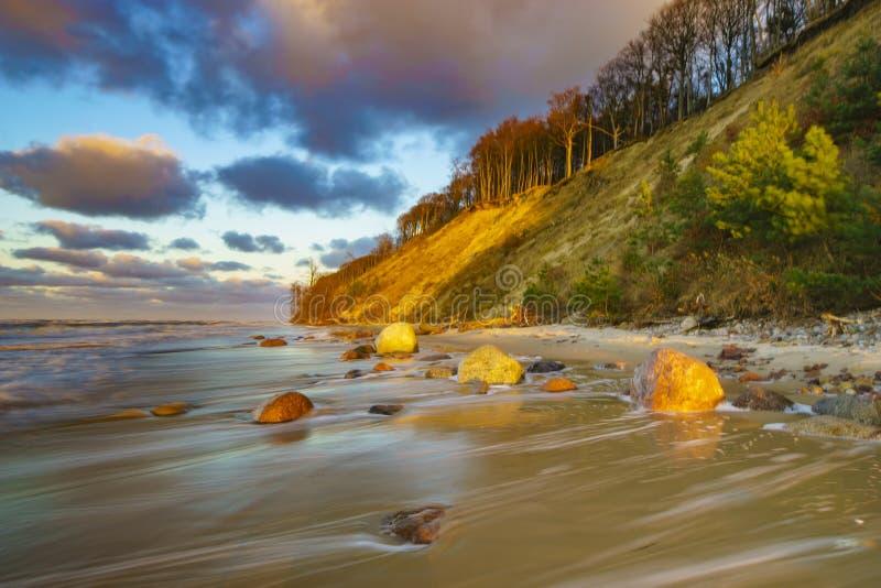 Zonsondergang over het strand en de klippen in het Nationale Park van Wolinski, Balt stock afbeeldingen