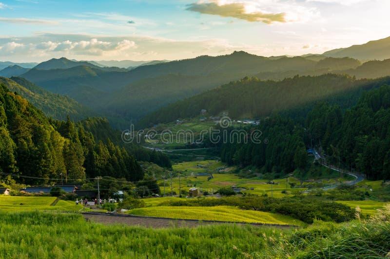 Zonsondergang over Japans platteland met bergen en padievelden stock fotografie